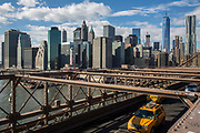 Two New York yellow taxicabs drive across the iconic Brooklyn Bridge away from Lower Manhattan, New York City, United States of America.  The sky scrapers of the financial district called Downtown Manhattan, can be seen in the background.