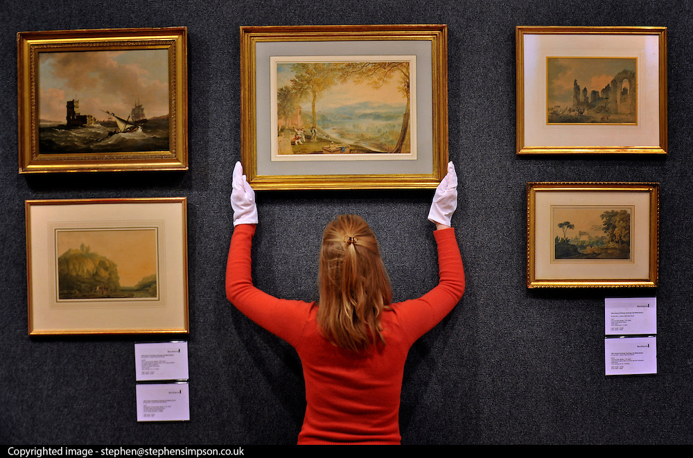 © Licensed to London News Pictures. 23/01/2012, London, UK. An employee straightens 'Kirkby Lonsdale Churchyard' by Joseph Mallord William Turner RA (1775-1851). The watercolour shows a typical English landscape and has not been seen at auction since 1884. It is estimated to fetch 200,000-300,000GBP. Photo call at Bonhams auctioneers in Central London for 19th Century Paintings sale.  Photo credit : Stephen Simpson/LNP
