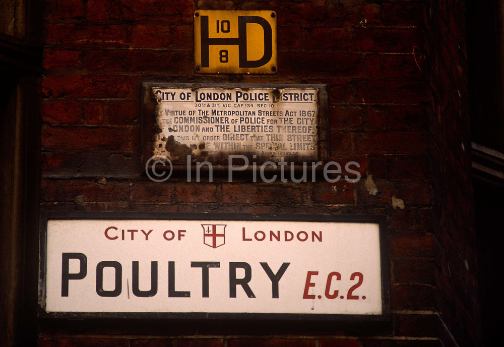 """An old City of London street sign for Poultry EC2 beneath a rusting police bylaws sign on a late 1980s brick wall. Before the older signage was replaced in the mid-1990s for more modern architecture, these signs will have disappeared or available through vintage auctions. Poultry is a short street in the City of London. It is an eastern continuation of Cheapside, between Old Jewry and Mansion House Street, near Bank junction. It takes its name, like other medieval roads nearby such as Milk Street and Bread Street, from the various produce once sold at Cheapside, meaning """"market-place"""" in Old English. The street gave its name to a prison, Poultry Compter, once located there."""