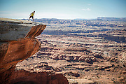 SHOT 10/16/16 12:39:43 PM - Taking in the view atop a mesa at White Crack during a White Rim mountain biking trip in Canyonlands National Park just outside of Moab, Utah. The White Rim Road is a 71.2-mile-long unpaved four-wheel drive road that traverses the top of the White Rim Sandstone formation below the Island in the Sky mesa of Canyonlands National Park in southern Utah in the United States. The road was constructed in the 1950s by the Atomic Energy Commission to provide access for individual prospectors intent on mining uranium deposits for use in nuclear weapons production during the Cold War. Four-wheel drive vehicles and mountain bikes are the most common modes of transport though horseback riding and hiking are also permitted.<br /> (Photo by Marc Piscotty / © 2016)