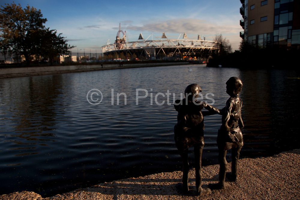 Tiny bronze sculptures look across the Lea Navigational Canal towards the Olympic Stadium in East London.