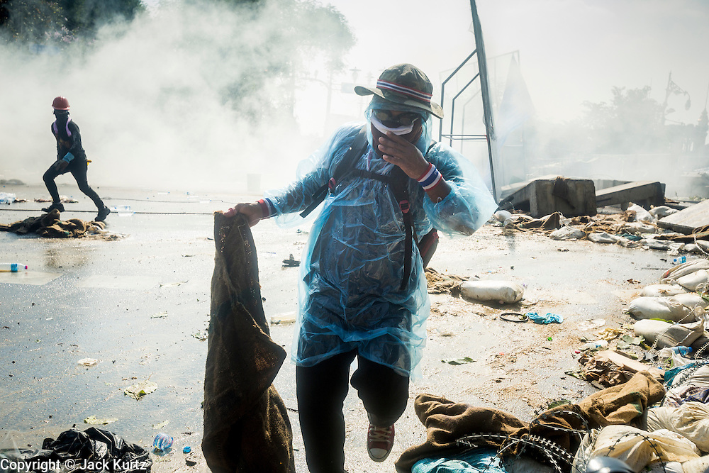 02 DECEMBER 2013 - BANGKOK, THAILAND: Anti-government protestors walk through a cloud of tear gas in Bangkok. Anti-government protestors and Thai police continued to face off Monday for a second day. Police used tear gas, water cannons and rubber bullets against protestors who charged their positions near the barriers on Chamai Maruchet bridge on Phitsanulok Road, which leads to the Government House.     PHOTO BY JACK KURTZ