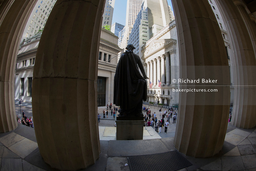 George Washington statue and distorted fish-eye lens of classical pillars of the New York Stock Exchange (NYSE) on Wall Street, Lower Manhattan,.