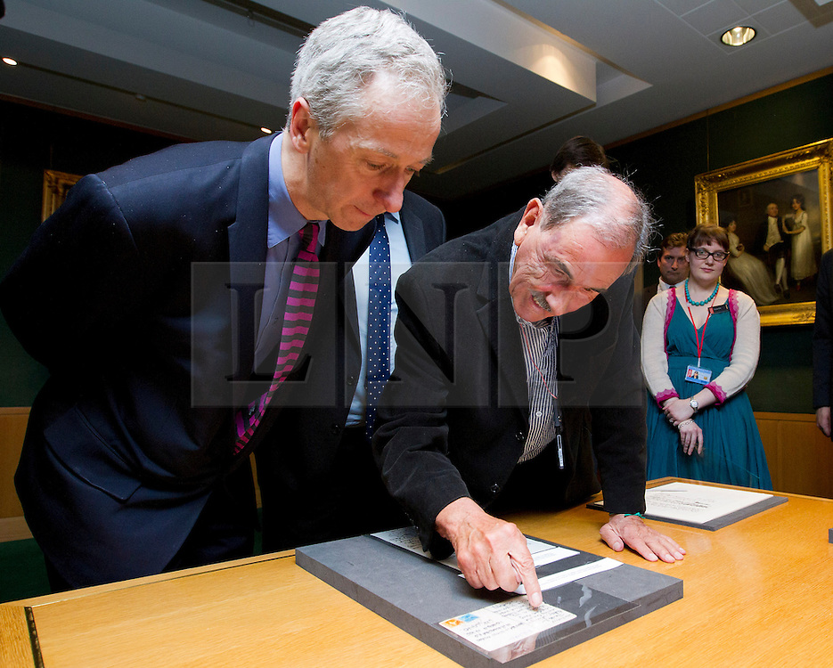"""© Licensed to London News Pictures. 22/05/2013. London, UK. Hunter Davies, the acclaimed Beatles biographer and Roly Keating, the chief executive of the British Library, look at a postcard sent to Hunter and his wife by John and Cynthia Lennon in 1968 at the British Library in London today (22/05/2013). The postcard is part of manuscripts and lyrics donated to the library under the """"lifetime giving"""" scheme. Photo credit: Matt Cetti-Roberts/LNP"""