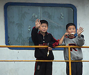 Two North Korean boys eat ice cream and wave at a Chinese tourist boat in the Border town of Sunuiju October 10, 2006.  DPRK, north korea, china, dandong, border, liaoning, democratic, people's, rebiblic, of, korea, nuclear, test, rice, japan, arms, race, weapons, stalinist, communist, kin jong il