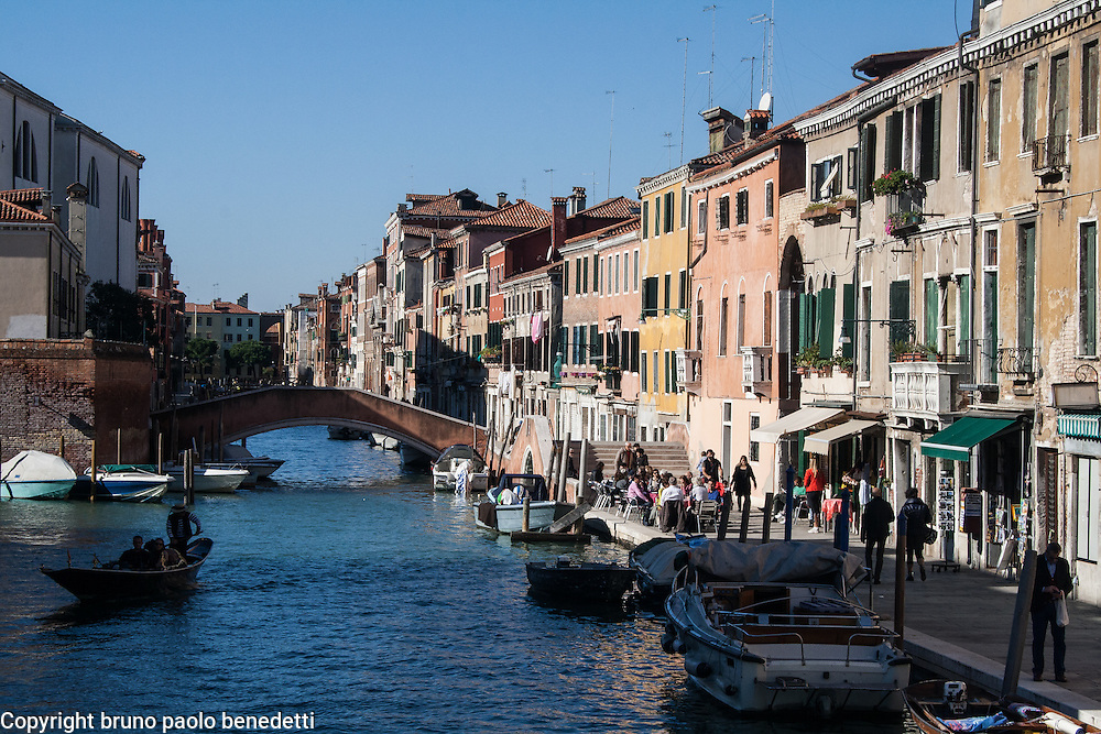 view of buildings in Jewish ghetto of venice in italy, with channel, boats, bridge and gondolas