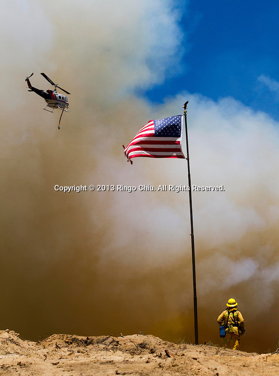A firefighter keep watches as a helicopter prepares to make a water drop onto a wildfire, Friday May 31, 2013, near Castiac, California. Fourteen aircraft and more than 550 firefighter were deployed in a ground and air campaign against a brush fire that has blackened about 1,500 acres in sparsely populated San Francisquito Canyon in the Angeles National Forest northeast of Santa Clarita. The Powerhouse Fire, which broke out Thursday afternoon, was about 15 percent contained. The estimated date of full containment is Wednesday, June 5. (Photo by Ringo Chiu/PHOTOFORMULA.com)