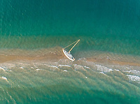 Aerial view of a small sailboat stranded on sandbank in the Gulf of Patras, Greece.