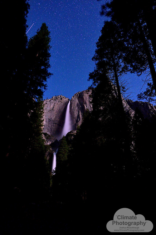 The International Space Station passes over Yosemite Falls at night.