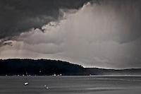 Rain streams from an omnious dark nimbus cloud over the Hood Canal of Puget Sound, Washington, USA