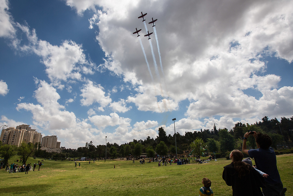 People watch Israeli Air Force Aerobatic Team fly over Sacher Park during Israel's 67th Independence Day in Jerusalem, on April 23, 2015, Israel is celebrating its annual Independence Day, marking 67 years since the creation of the Jewish state in 1948.