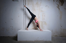 Mid adult woman practicing one legged downward facing dog position on concrete block, Munich, Bavaria, Germany