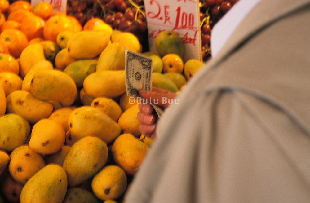 Man standing by mangos paying for fruit