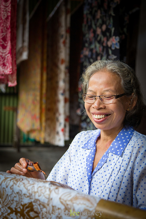 Woman applying wax for the Batik process, wax resistant dyeing, Yogyakarta, Yogyakarta Special Region, Java, Indonesia, Southeast Asia