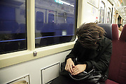 young adult man sleeping while commuting on a train Tokyo Japan