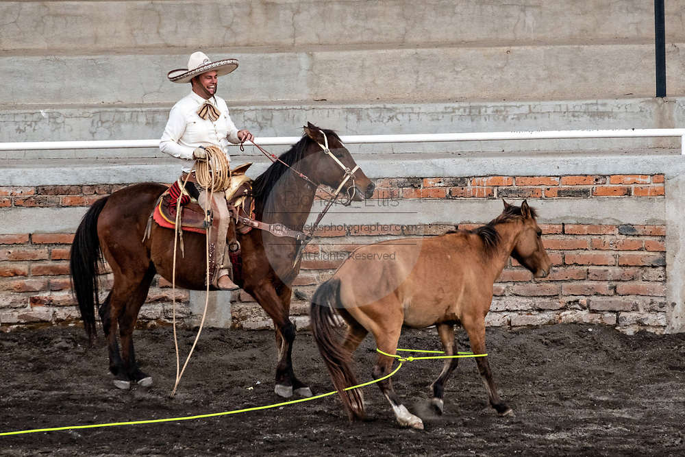 Juan Franco, Sr., smiles proudly after his eight-year-old son Juan Franco, successfully ropes a wild mare, during a practice session in the Jalisco Highlands town of Capilla de Guadalupe, Mexico. The roping event is called Manganas a Pie or Roping on Foot and involves a charro on foot roping a wild mare by its front legs to cause it to fall and roll once. The wild mare is chased around the ring by three mounted charros.