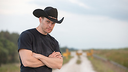 portrait of a rugged cowboy with his arms crossed while standing on a dirt road