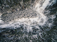 Aerial view of an Estonian forest and a frozen river covered with snow during winter.