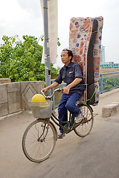Man With Materess On Bicycle