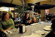 Family enjoying al fresco dining at night. The Rocks, Sydney, Australia