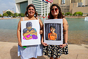 """Sisters and DACA young people Pamela and Diana Rubio hold illustrations by artist Kalyn Duke during the Fammiles Belong Together Rally in Dallas Tx. Their father was deported to Mexico two years ago. """"We have been to the processing center when you are deported. We know this from experience"""" said Pamela."""