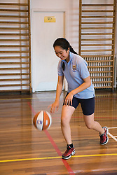 Secondary school student bouncing a ball in a game of basketball,
