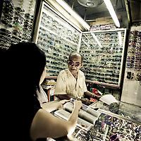 Sunglass salesman sporting cool shades in market, Saigon, Vietnam