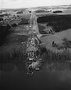 """Y-530407A-2. """"New Wilsonville Highway (I-5) Baldock freeway. Under construction. Ground graded, bridge under construction. April 7, 1953"""", """"Work. Preliminary construction, including cofferdams, for Willamette bridge makes a foreground for this picture showing how highway lanes will be separated. Wilsonville is at upper left in this shot, which, when joined to one above, gives a view of entire section of the new superhighway from Willamette to Tualatin."""" Caption published in Oregonian, April 26 1953"""
