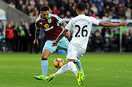 Burnley's Andre Gray (L) scores Burnley's second goal whist being challenged by Swansea's Kyle Naughton. Premier league match, Swansea city v Burnley at the Liberty Stadium in Swansea, South Wales on Saturday 4th March 2017.<br /> pic by  Carl Robertson, Andrew Orchard sports photography.