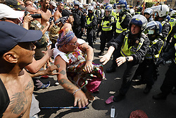 © Licensed to London News Pictures. 19/07/2021. London, UK. A protester is pushed over by police in riot gear as they hold back protesters trying to reach Whitehall from Parliament Square in central London on Freedom Day. All covid regulations in England are being scrapped from today even though infections and hospitalisations are on the increase. Photo credit: Peter Macdiarmid/LNP