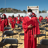 Camron Roman stands with fellow graduates for the national anthem at the University of New Mexico-Gallup Spring 2021 commencement ceremony at Angelo DiPaolo Memorial Stadium in Gallup Friday morning. Roman is a McKinley Academy graduate who graduated with an Associate of Applied Science degree from UNM-Gallup.