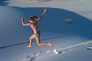 Young woman leaping down a sand dune at White Sands National Monument, New Mexico, USA
