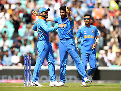 India's Jasprit Bumrah (centre) celebrates with Virat Kohli (left) after taking the wicket of New Zealand's Colin Munro during the ICC Cricket World Cup Warm up match at The Oval, London.