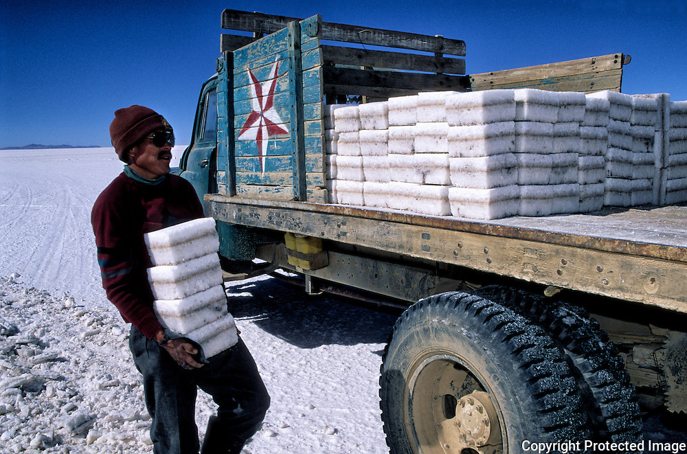 After three days of work Inocencio  Flores will have cut up to thousand blocks of salt that was going even colchani in his(her,your) truck.  Salar de Uyuni ( Uyuni salt flat ) . Department  of Potosí  ( Los Lipez).  South West  Bolivia. <br /> Adult Altiplano America Andes Arid  Aridity Axe Barren  Bicycle Block  Bolivia Cleaver Color Colour Cone  Day Daytime  Department  Desert Desolate Desolation Dry  Exterior Extraction  Geography Hack Hard Hatchet  Heat Highlands  Horizon Horizontal Human  Latin America Lake  Los Lipez  Lorry Male Man Men Miner Mining Nature  Resource  Natural  One Outdoors Outside  Pan People  Person Pyramide Potosí  Production  Region Resource Rural Salar de Uyuni  Salt Flat  Salt Pan  Salt lake  Scenic Seasoning  Single Shape South America  Southwest  Sud Sunglasses  Surface Travel Track West White Work  Worker Working