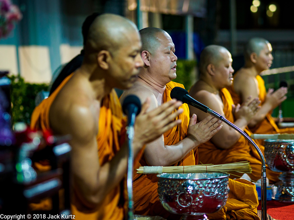 """01 MARCH 2018 - BANGKOK, THAILAND:    Buddhist monks lead a merit making ceremony at Wat Pathum Wanaram in central Bangkok. Many people go to temples to perform merit-making activities on Makha Bucha Day, which marks four important events in Buddhism: 1,250 disciples came to see the Buddha without being summoned, all of them were Arhantas, or Enlightened Ones, and all were ordained by the Buddha himself. The Buddha gave those Arhantas the principles of Buddhism. In Thailand, this teaching has been dubbed the """"Heart of Buddhism.""""    PHOTO BY JACK KURTZ"""