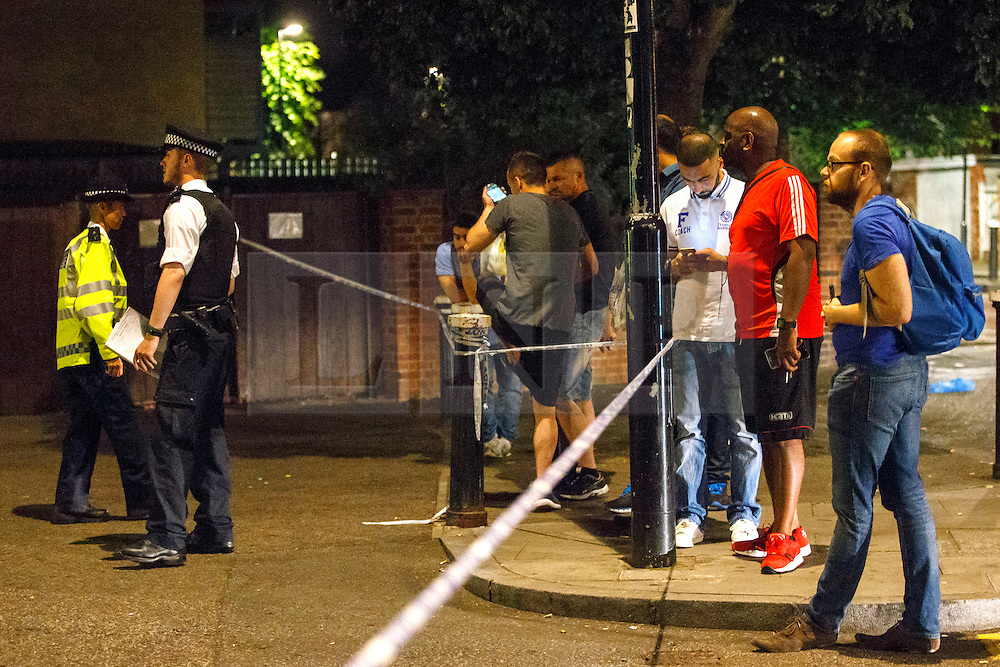 © Licensed to London News Pictures. 10/07/2015. London, UK. People watching forensic officers investigating a crime scene on Lordship Lane in Wood Green, north London where a man has died and a woman has been taken to hospital following an apparent drive-by shooting on Friday, July 10, 2015. Photo credit: Tolga Akmen/LNP