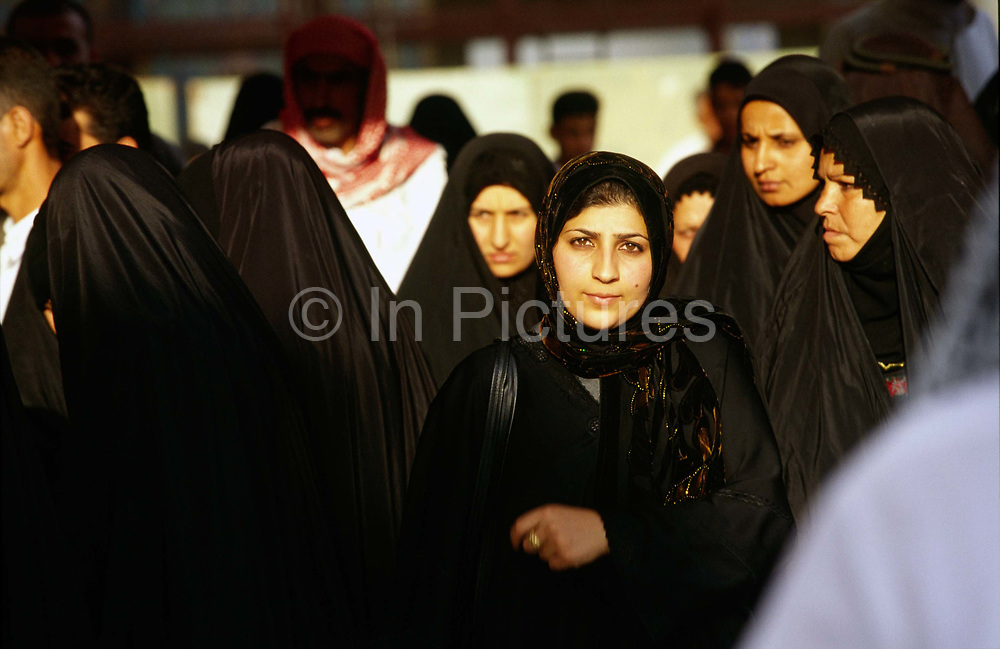 Female pilgrims at the shrine in Karbala, Iraq. The shrine is holy to Shi'ite Muslims because it contains the tomb of Mashad al Hasayn bin Ali (Hussein), the grandson of the Prophet Muhammad by his daughter Fatima and Ali ibn Abi Talib.<br /> Husain's tomb is a place of pilgrimage for many Shi'a Muslims, especially on Ashura. Many elderly pilgrims travel there to await death, as they believe the tomb to be one of the gates to paradise.