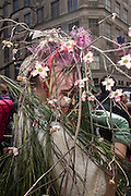New York, NY, USA-27 March 2016. A woman hidden behind flowers and broom in the annual Easter Bonnet Parade and Festival.