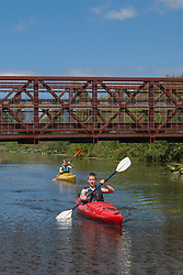 United States, Washington, Bellevue, teenage boy and girl kayaking under bridge in Mercer Slough Nature Park.  MR