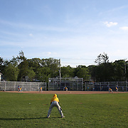 A young fielder playing centre field watches the action during the Norwalk Little League baseball competition at Broad River Fields,  Norwalk, Connecticut. USA. Photo Tim Clayton