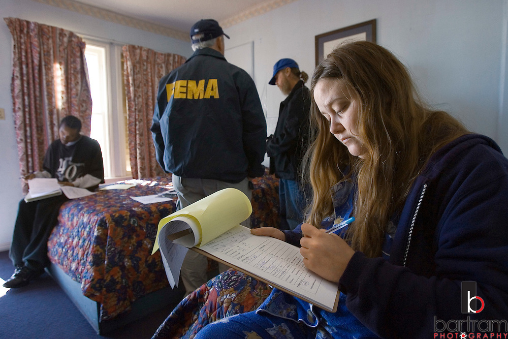 KEVIN BARTRAM/The Daily News.Teri Garrett, right, fills out FEMA paperwork at the Surf Motel in the 900 block of Avenue M in Galveston on Thursday, Dec. 15, 2005. Garrett moved out of her apartment in the 900 block of Avenue K and into the motel following Hurricane Rita. Workers from FEMA visited Galveston hotels and motels housing evacuees on Thursday.