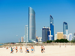 Volleyball game on Corniche beach with skyline in Abu Dhabi United Arab emirates