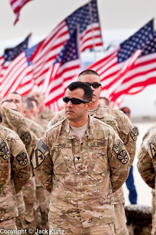 """15 JANUARY 2012 - PHOENIX, AZ:    Soldiers stand in formation while American flags flutter in the wind at the The 161st Air Refueling Wing of the Arizona Air National Guard in Phoenix. About 100 soldiers of A (Alpha) Company of the 422nd Expeditionary Signal Battalion (referred to as """"Alpha 4-2-2"""") of the Arizona Army National Guard returned to Arizona on Sunday, Jan. 15, following a nearly year-long deployment to Afghanistan. More than 10,000 Arizona Army and Air National Guard Soldiers and Airmen have been ordered to federal active duty in support of Operations Noble Eagle, Enduring Freedom, Iraqi Freedom, and New Dawn since September 2001. Approximately 200 Arizona National Guard Soldiers and Airmen are still serving on federal active duty overseas.  PHOTO BY JACK KURTZ"""