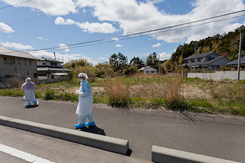 A Japanese couple in makeshift radiation suits visit their house for the last time in the town of Tomioka, Futaba District of Fukushima, Japan. Thursday May 2nd 2013. The town was evacuated on March 12th after the March 11th 2011 earthquake and tsunami cause meltdowns at the nearby Fukushima Daichi nuclear power station. It lies well within the 20 kms exclusion zone though parts of the town have recently been opened again to allow locals to visit their property during daylight hours.