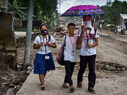"""22 JANUARY 2018 - GUINOBATAN, ALBAY, PHILIPPINES: Students in Guinobatan wear face masks while they walk home. Several communities in Guinobatan were hit ash falls from the eruptions of the Mayon volcano and many people wore face masks to protect themselves from the ash. There were a series of eruptions on the Mayon volcano near Legazpi Monday. The eruptions started Sunday night and continued through the day. At about midday the volcano sent a plume of ash and smoke towering over Camalig, the largest municipality near the volcano. The Philippine Institute of Volcanology and Seismology (PHIVOLCS) extended the six kilometer danger zone to eight kilometers and raised the alert level from three to four. This is the first time the alert level has been at four since 2009. A level four alert means a """"Hazardous Eruption is Imminent"""" and there is """"intense unrest"""" in the volcano. The Mayon volcano is the most active volcano in the Philippines. Sunday and Monday's eruptions caused ash falls in several communities but there were no known injuries.    PHOTO BY JACK KURTZ"""