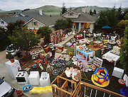 The Caven Family with all of their material possessions, except for more boxes of books stored in the garage, American Canyon, California. Craig Caven, Regan Ronayne and their two children, Andrea and Ryan live in a multi-cultural bedroom community called American Canyon, California, about one hour north of San Francisco. The photograph was made by Peter Menzel and patterned after his 1994 book, Material World: A Global Family Portrait.