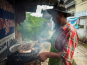 18 SEPTEMBER 2015 - BANGKOK, THAILAND: A vendor makes grilled catfish at his stand in the neighborhood near Wat Kalayanamit. Fiftyfour homes around Wat Kalayanamit, a historic Buddhist temple on the Chao Phraya River in the Thonburi section of Bangkok are being razed and the residents evicted to make way for new development at the temple. The abbot of the temple said he was evicting the residents, who have lived on the temple grounds for generations, because their homes are unsafe and because he wants to improve the temple grounds. The evictions are a part of a Bangkok trend, especially along the Chao Phraya River and BTS light rail lines. Low income people are being evicted from their long time homes to make way for urban renewal.             PHOTO BY JACK KURTZ