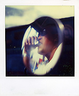 Old Polaroid photo of a man wearing sunglasses and biting his thumb reflected in a small round mirror, Palawan Island, Philippines, Southeast Asia