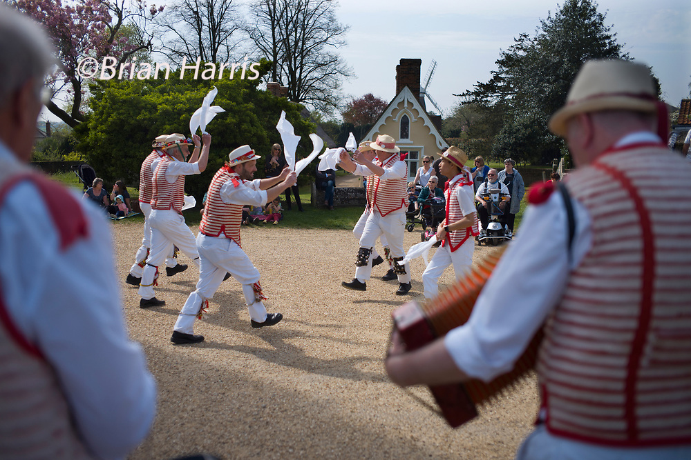 Thaxted Essex England UK 22 April 2019. Traditional Easter Bank Holiday Monday Morris Dancing in Thaxted Church Yard.<br /> Thaxted Morris in red and white along with guest side Devils Dyke Morris side from Cambridgeshire entertain the crowd in the sopring sunshine.