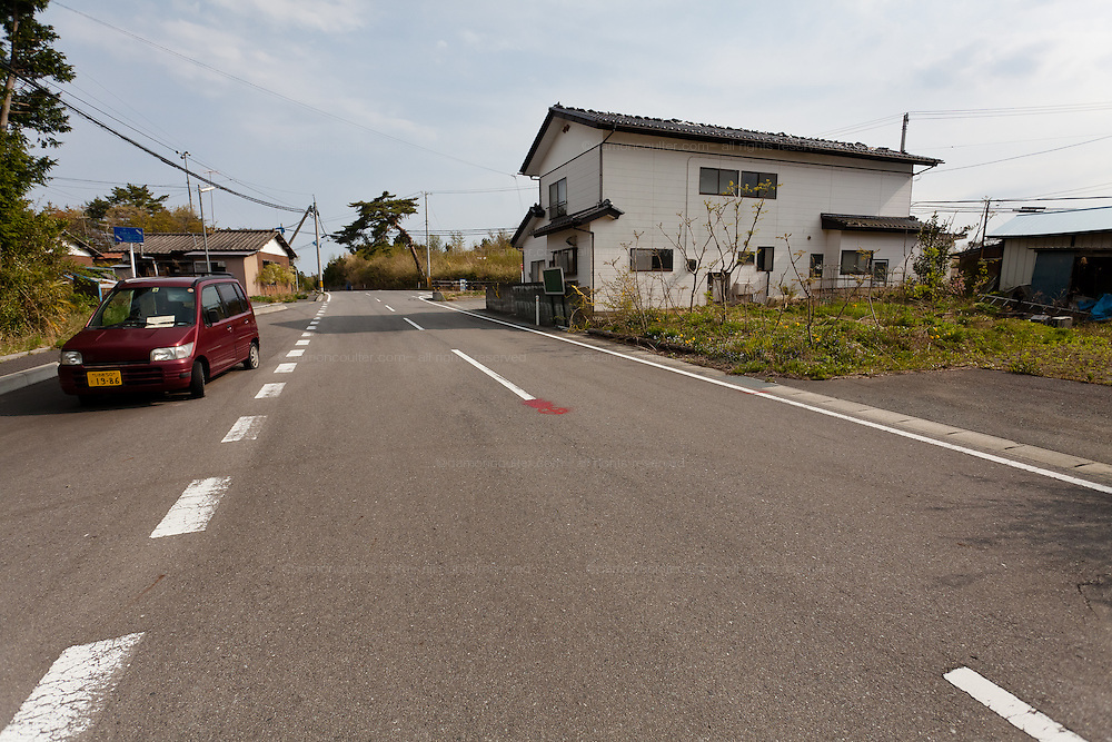 Abandoned cars and houses in the town of Tomioka, Futaba District of Fukushima, Japan. Monday April 29th 2013. The town was evacuated on March 12th after the March 11th 2011 earthquake and tsunami cause meltdowns at the nearby Fukushima Daichi nuclear power station. It lies well within the 20 kms exclusion zone though parts of the town have recently been opened again to allow locals to visit their property during daylight hours.